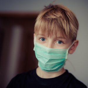 Child with blonde hair and black shirt, wearing mask at the dentist office.