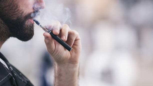 bearded man vaping an e cigarette